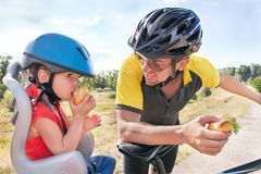 Happy father and son is eating lunch (snack) during bicycle ride. Child (boy) and men have biking helmets. The son is in the bicycle chair (seat). Caucasian Royalty Free Stock Photography