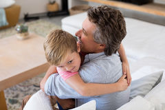 Happy father and son embracing each other in living room Royalty Free Stock Images