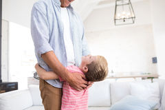 Happy father and son embracing each other in living room Stock Image
