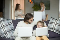 Happy father and son embracing using laptops together at home. Smiling dad and boy bonding holding computers sitting on sofa, kid imitating copying daddy with royalty free stock photography
