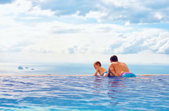 Happy father and son enjoy beautiful seascape from infinity pool, vacation concept Stock Photo