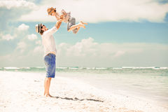 Happy father and son enjoying beach time on summer Stock Photos