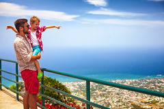 Happy father and son enjoying the fascinating view on Atlantic ocean coastline from observation deck of Pico Isabel de Torres. Cheerful father and son enjoying Royalty Free Stock Image