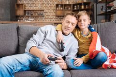 Happy father and son falling asleep after gaming. Tired but happy. Pleasant young father and his little son cuddling each other on the sofa, holding game Stock Image