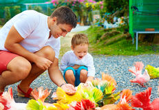 Happy father and son feeding colorful pigeons on animal farm Stock Photo