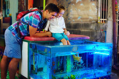 Happy father and son at fish pedicure treatment at street market Royalty Free Stock Image