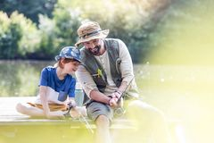 Happy father and son fishing in lake while sitting on pier stock photography