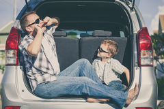 Happy father and son getting ready for road trip on a sunny day Royalty Free Stock Photo