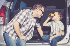 Happy father and son getting ready for road trip on a sunny day Stock Photos