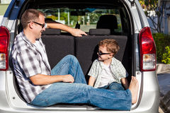 Happy father and son getting ready for road trip on a sunny day. Stock Images