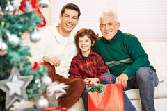 Father and son with grandfather at christmas. Happy father and son with grandfather at christmas with gifts royalty free stock photo