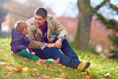 Happy father and son having fun in autumn park Stock Images