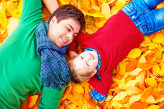 Happy father and son having fun in autumn park Stock Photos