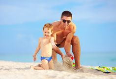 Happy father and son having fun on the beach Stock Photos