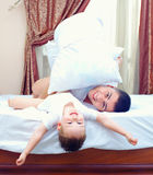 Happy father and son having fun in bed room Stock Image