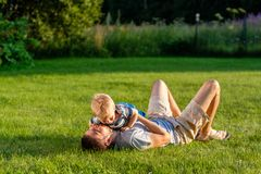 Happy father and son having fun outdoor on meadow Stock Images