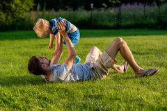 Happy father and son having fun outdoor on meadow Royalty Free Stock Images