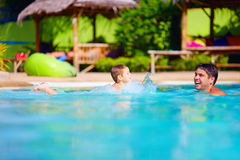 Happy father and son having fun in pool water, summer holiday Royalty Free Stock Photos