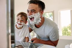 Happy father and son having fun while shaving. In bathroom. Young men and little boy with shaving foam on their faces looking into the bathroom mirror and Stock Photos