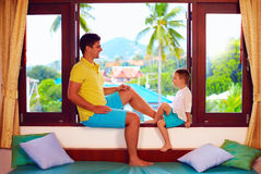 Happy father and son having fun, sitting on windowsill during vacation in tropics Royalty Free Stock Images
