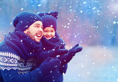 Happy father and son having fun under winter snow Royalty Free Stock Images