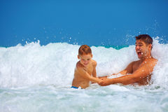 Happy father and son having fun in waves, summer vacation Royalty Free Stock Images
