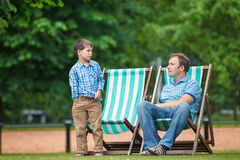 Happy father and son having rest in city park Stock Photo