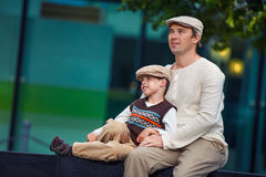 Happy father and son having rest outdoors in city Royalty Free Stock Photos