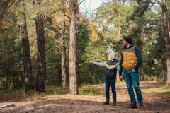 Happy father and son holding hands and looking away. In autumn forest Royalty Free Stock Photography