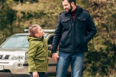 Happy father and son holding hands and smiling each other. In park Stock Photography