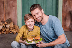 Happy father and son holding plate with homemade burgers Stock Image
