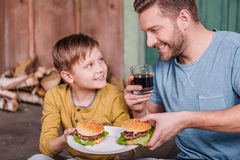 Happy father and son holding plate with homemade burgers Royalty Free Stock Photo