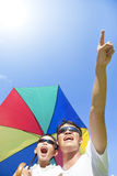 Happy father and son holding a umbrella with blue sky Stock Photo