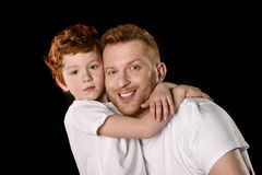 Happy father with son hugging and smiling at camera Stock Photos