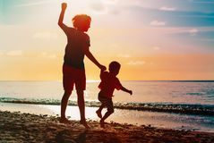 Father and son jumping at sunset beach. Happy father and son jumping at sunset beach Stock Images