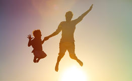 Happy father and son jumping at sunset sky Stock Images