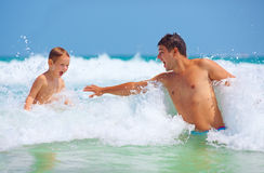 Happy father and son jumping in waves, summer vacation Stock Photography