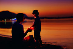 Happy father and son with lantern at sunset beach Royalty Free Stock Images