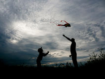 Happy father and little son launching a kite at sunset royalty free stock photos