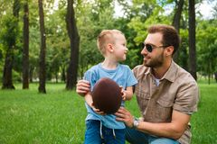 happy father and son looking at each other and holding american football ball