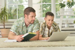 Father and son using laptop. Happy father and son lying on carpet and using laptop at home Stock Images