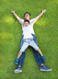 Happy father and son lying on a meadow together. In the park stock photos