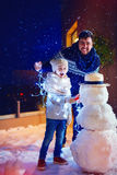 Happy father and son making snowman in backyard in the twilight Royalty Free Stock Images