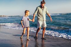 Happy father and son, man & boy child, running and having fun in the sand and waves on the beach. Happy father and son, men & boy child, running and having fun royalty free stock images