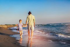 Happy father and son, man & boy child, running and having fun in the sand and waves on the beach. Happy father and son, men & boy child, running and having fun royalty free stock image