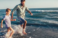 Happy father and son running and having fun in the beach. Happy father and son, men & boy child, running and having fun in the sand and waves of a sunny beach royalty free stock images