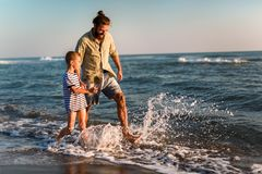 Father and son, man & boy child, running and having fun in the sand and waves of a sunny beach. Happy father and son, men & boy child, running and having fun in stock photos