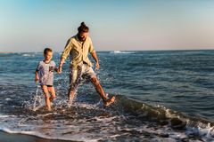 Father and son, man & boy child, running and having fun in the sand and waves of a sunny beach. Happy father and son, men & boy child, running and having fun in royalty free stock photos