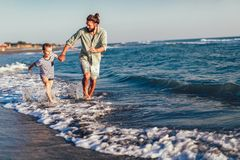 Happy father and son, man & boy child, running and having fun in the sand and waves on the beach. Happy father and son, men & boy child, running and having fun stock images