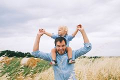 Happy father and son on nature at summer day. Family outdoors. Happy father and son. Family concept. Man and his little cute kid boy having fun on wheat field Royalty Free Stock Photography